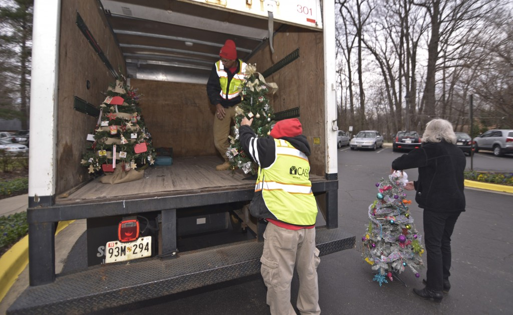 The team carefully unloads the decorated holiday trees