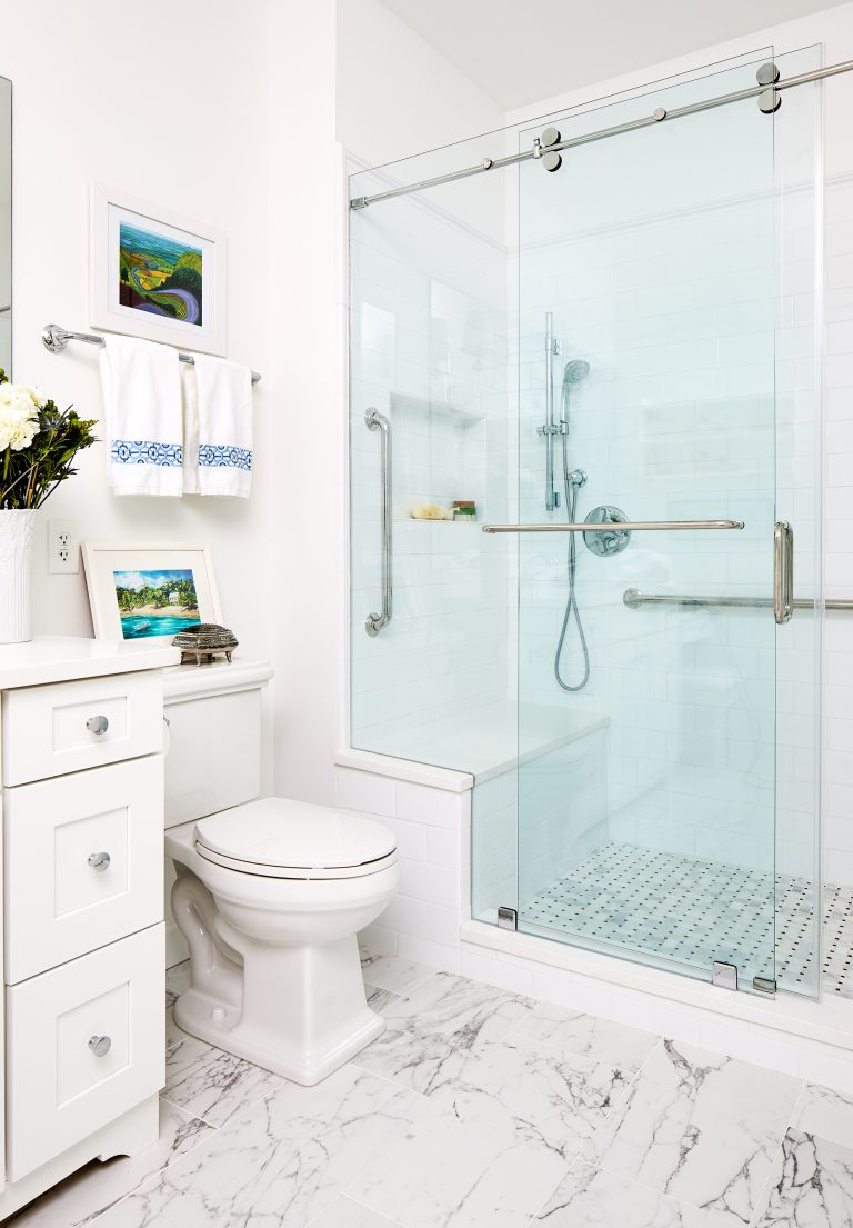shower with inbuilt sit-down area and marble tile floors with ceramic subway tile on the walls