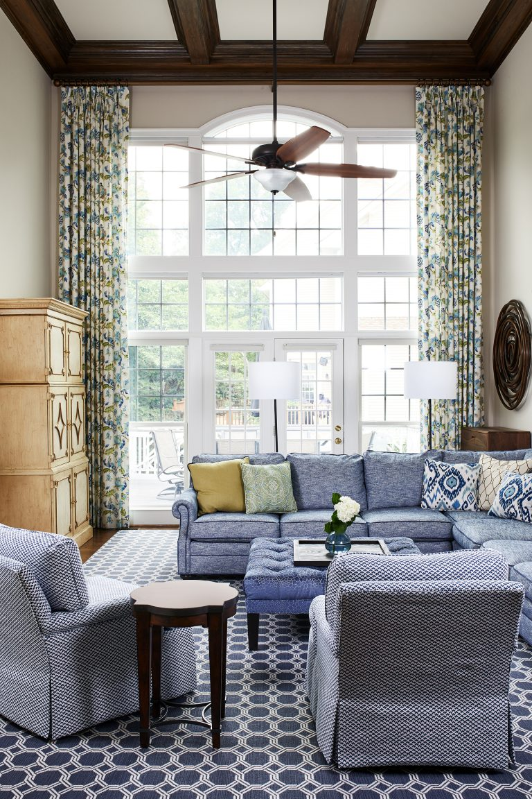 white and blue couches with two story windows, wooden ceiling fan with light and two floor lamps white shades