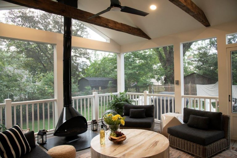 large patio with rusty wood beam, outdoor ceiling fan, wooden round table, fireplace