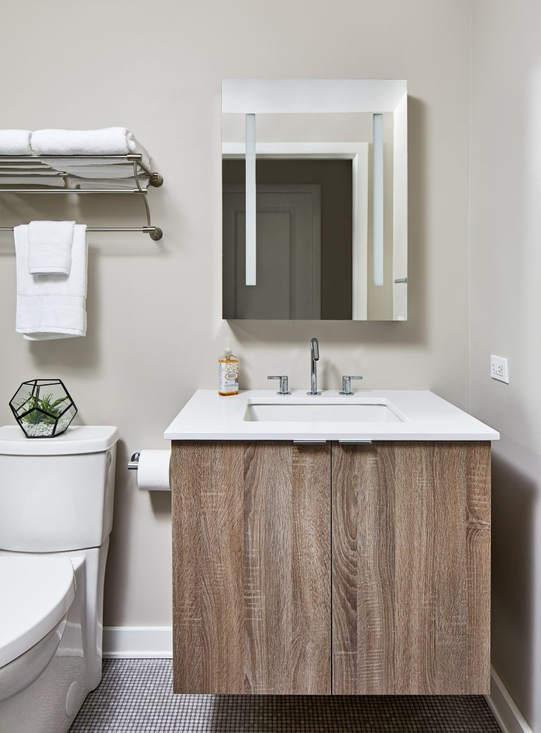 case design bathroom with single sink with cabinets doors above rectangular mirror