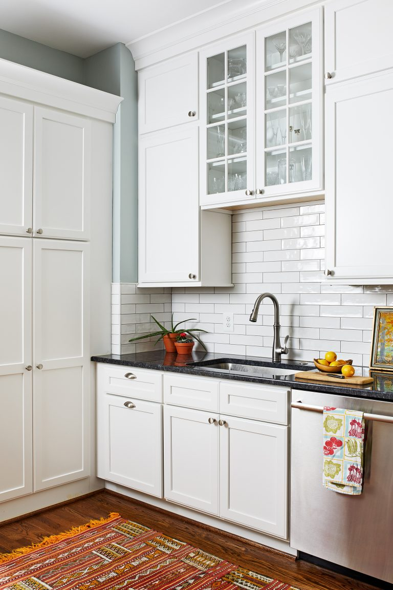 stainless undermount sink with black granite countertop, white tall kitchen cabinets, floating cabinets with glass doors
