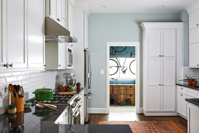 black granite countertop, and garage entry into kitchen custom wall white tall kitchen cabinets
