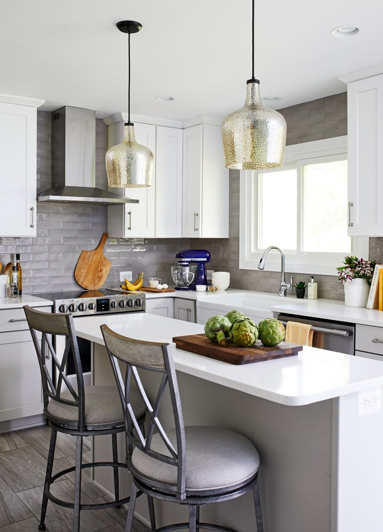 kitchen designer with glass hanging lights over white kitchen island with seating