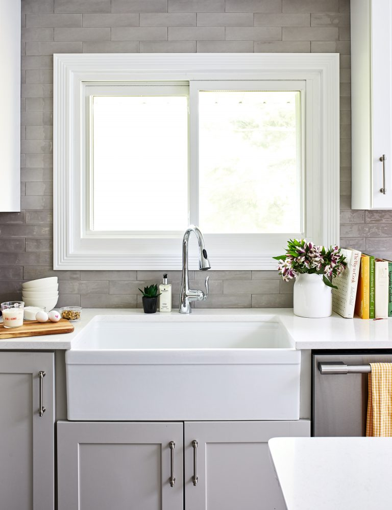 large farmhouse white sink above window with sliding doors