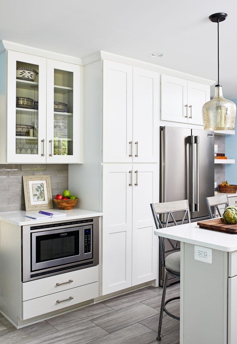 microwave under kitchen countertop and white cabinets with pull handles around the refrigerator