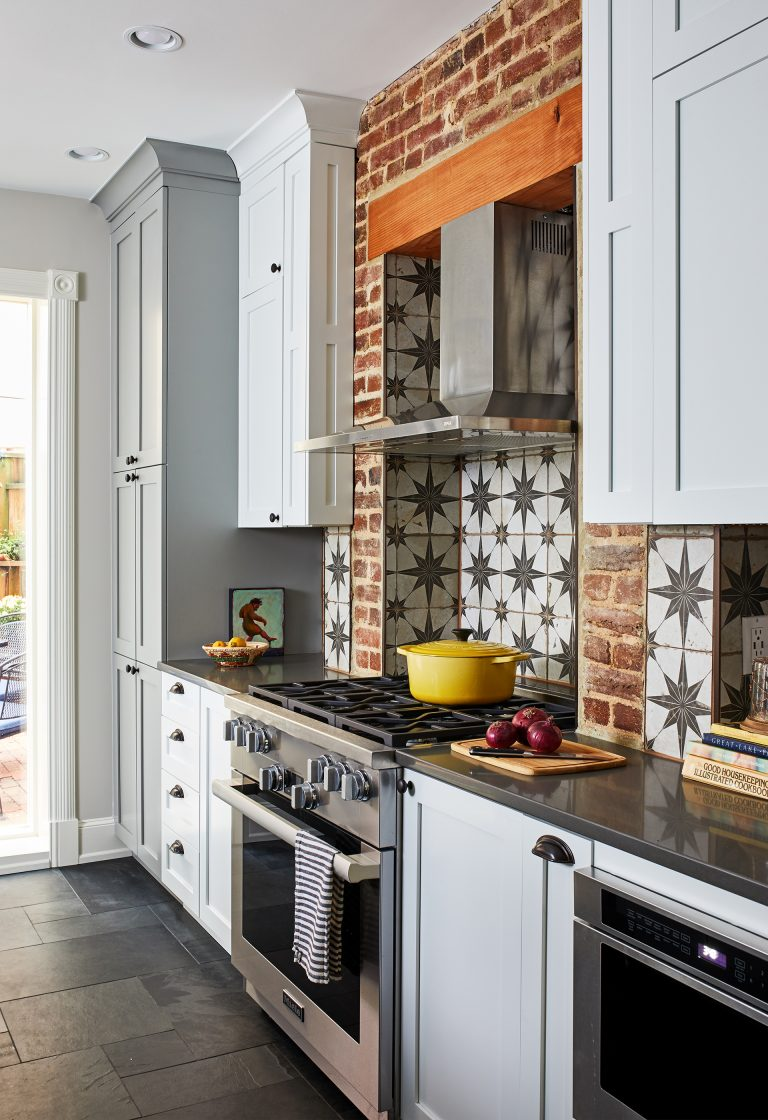 kitchen remodeling dc cabinets with round black knobs, slate flooring, gas range stove and star backsplash