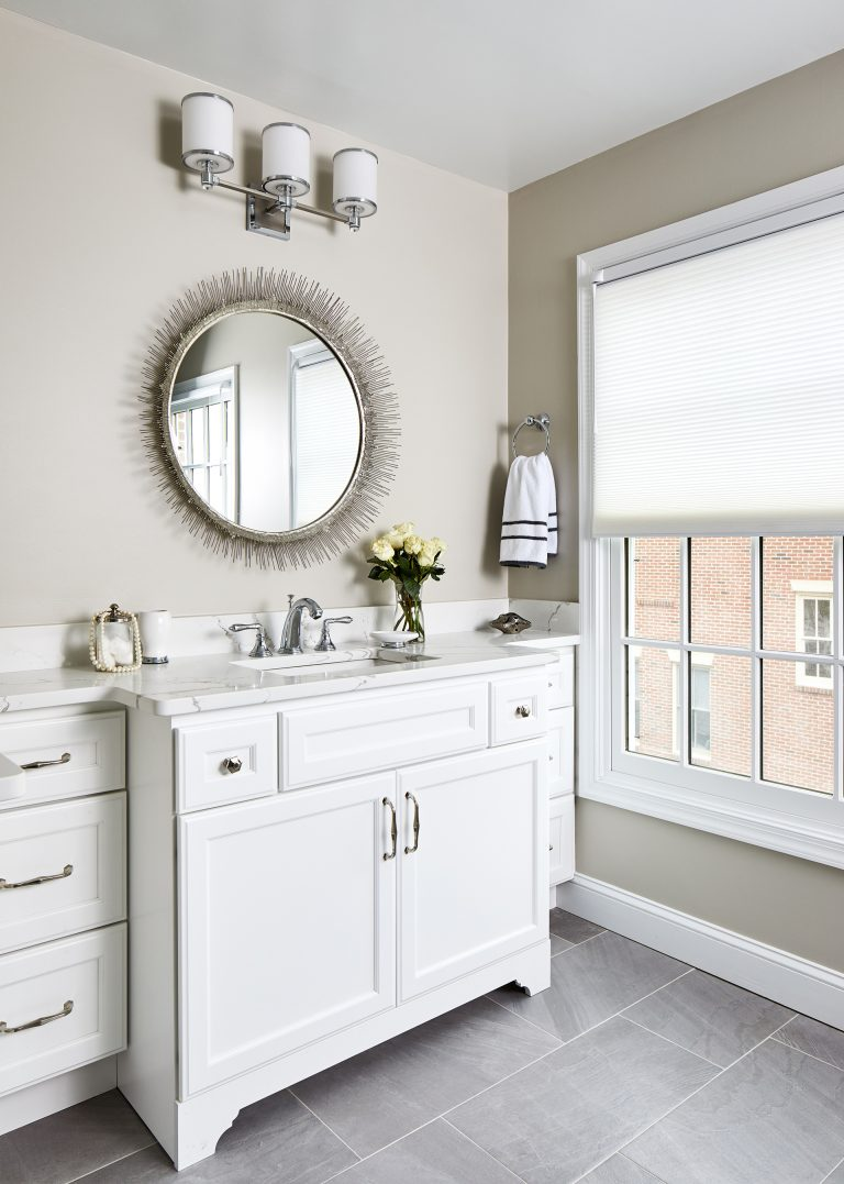 cabinet finish white bathroom with single sink and round wall mirror with traditional white framed windows