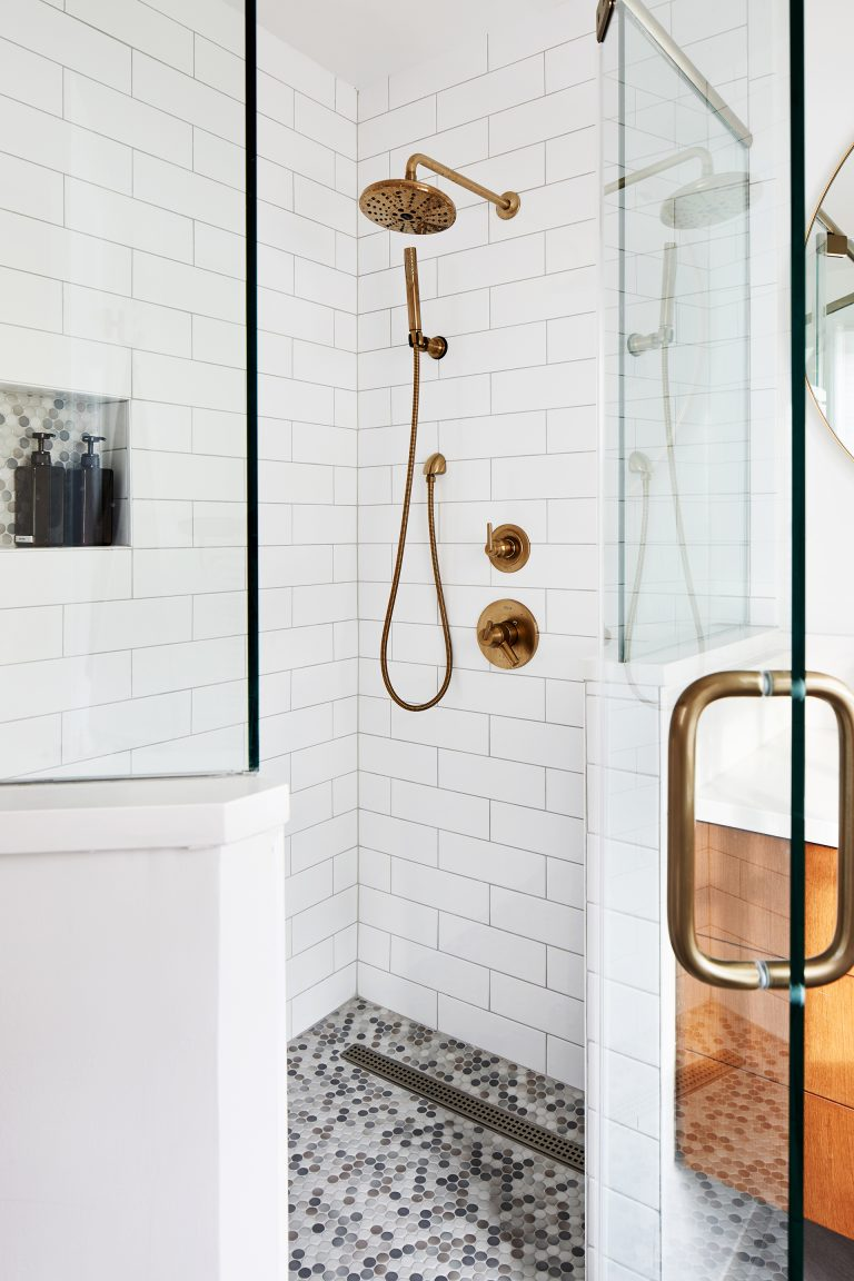 Walk in shower with glass shower door and gold fixtures against white brick tiles