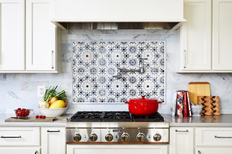 white paneled kitchen hood with blue and white back splash