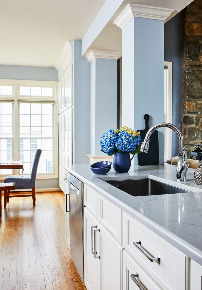 light blue kitchen counter with matching blue walls and white cabinets