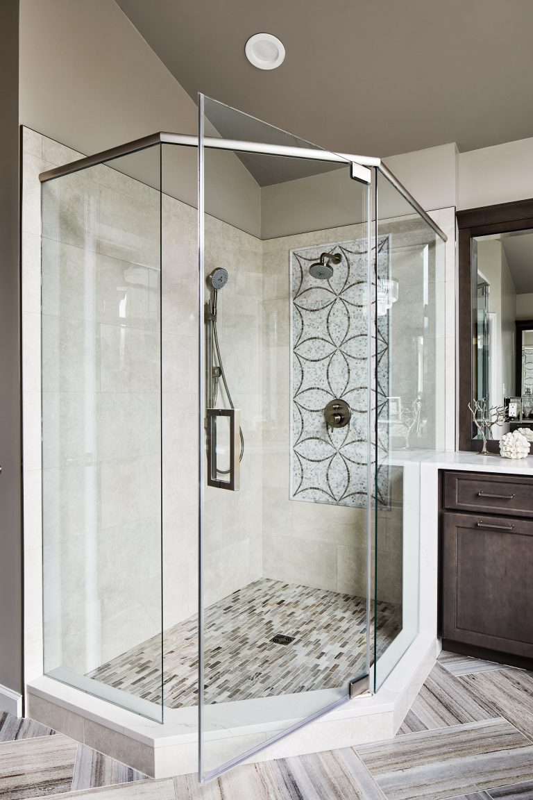 large shower is slightly elevated and enclosed in glass doors panels