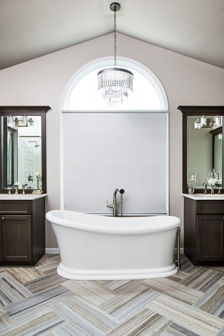 master bath with marble floor and stand along tub in between his and her vanity