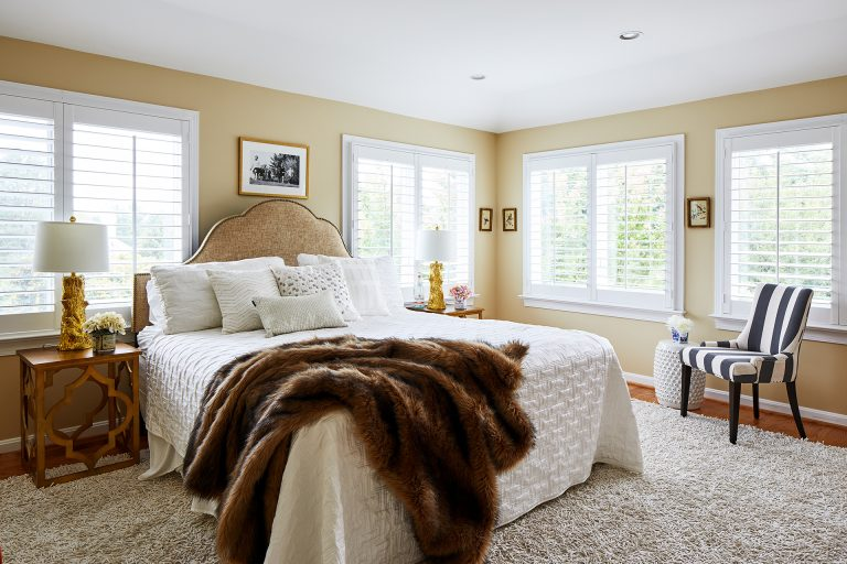 Master bed in front of lots of windows and two nightstands