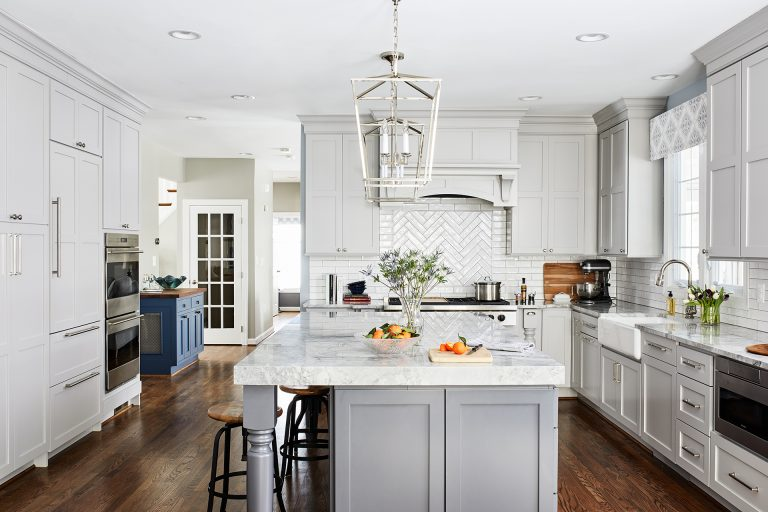 Large kitchen with lots of white cabinets lots of counter space and 4 light lantern pendant lamp above kitchen island with 2 stools