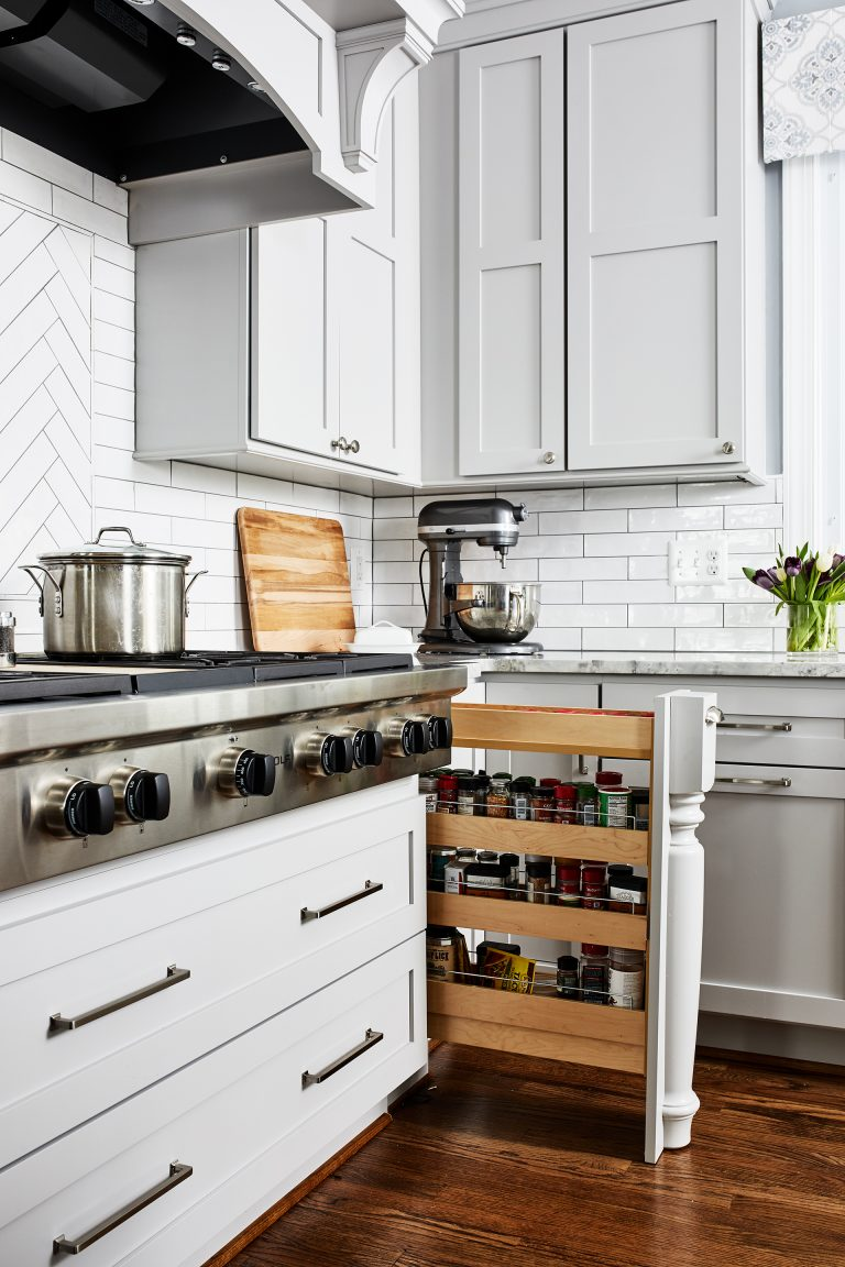 traditional design kitchen white cabinets with hidden spice rack next to stove