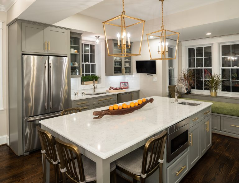 white kitchen island with gold bar stools