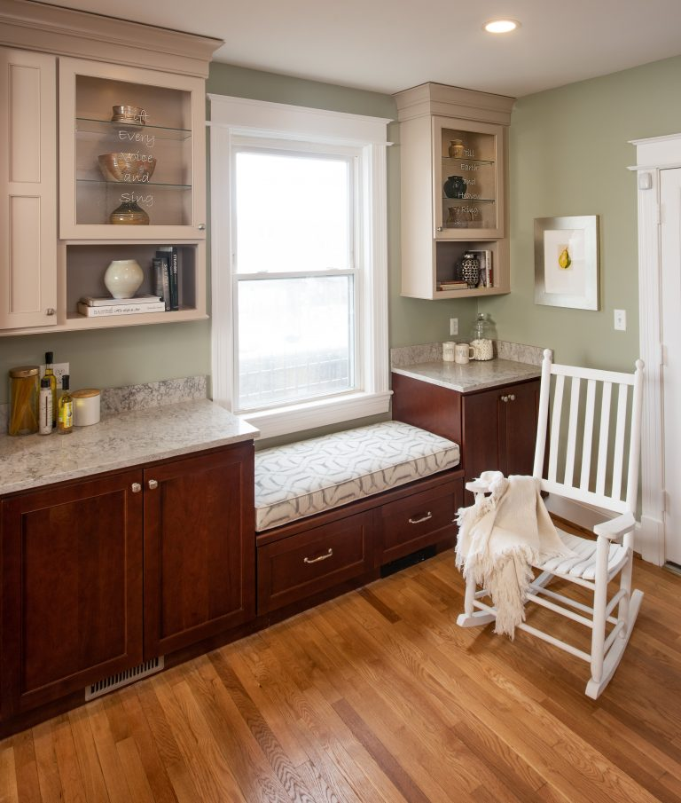 Bay window seat in kitchen with wood flooring and white see thru glass cabinets