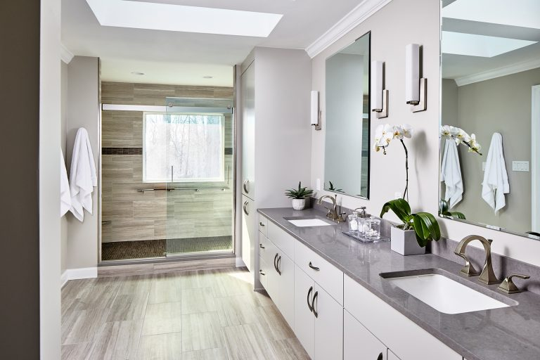 Large bathroom with white cabinets, double sink vanity, large shower with sliding doors and two frameless windows