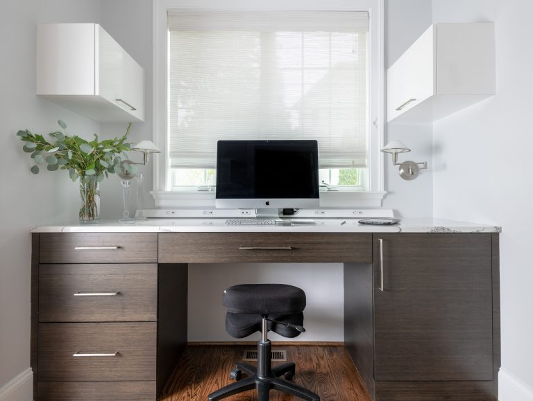 home office with desk under window, two side white cabinets facing window dressed in a white pull shade