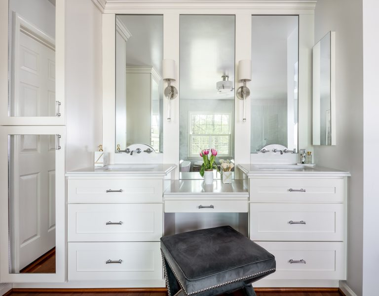 stunning master bathroom with white cabinets with white marble countertops flanking drop-down makeup vanity paired luxury stool and frameless mirrors